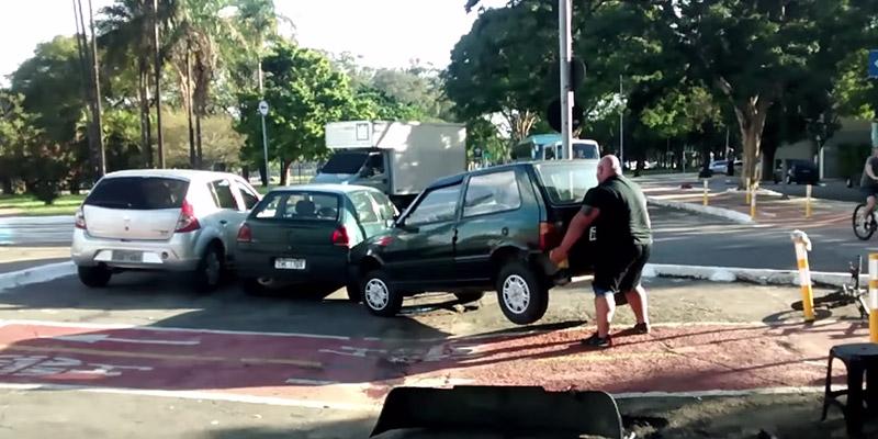 Un cycliste Brésilien déplace une voiture